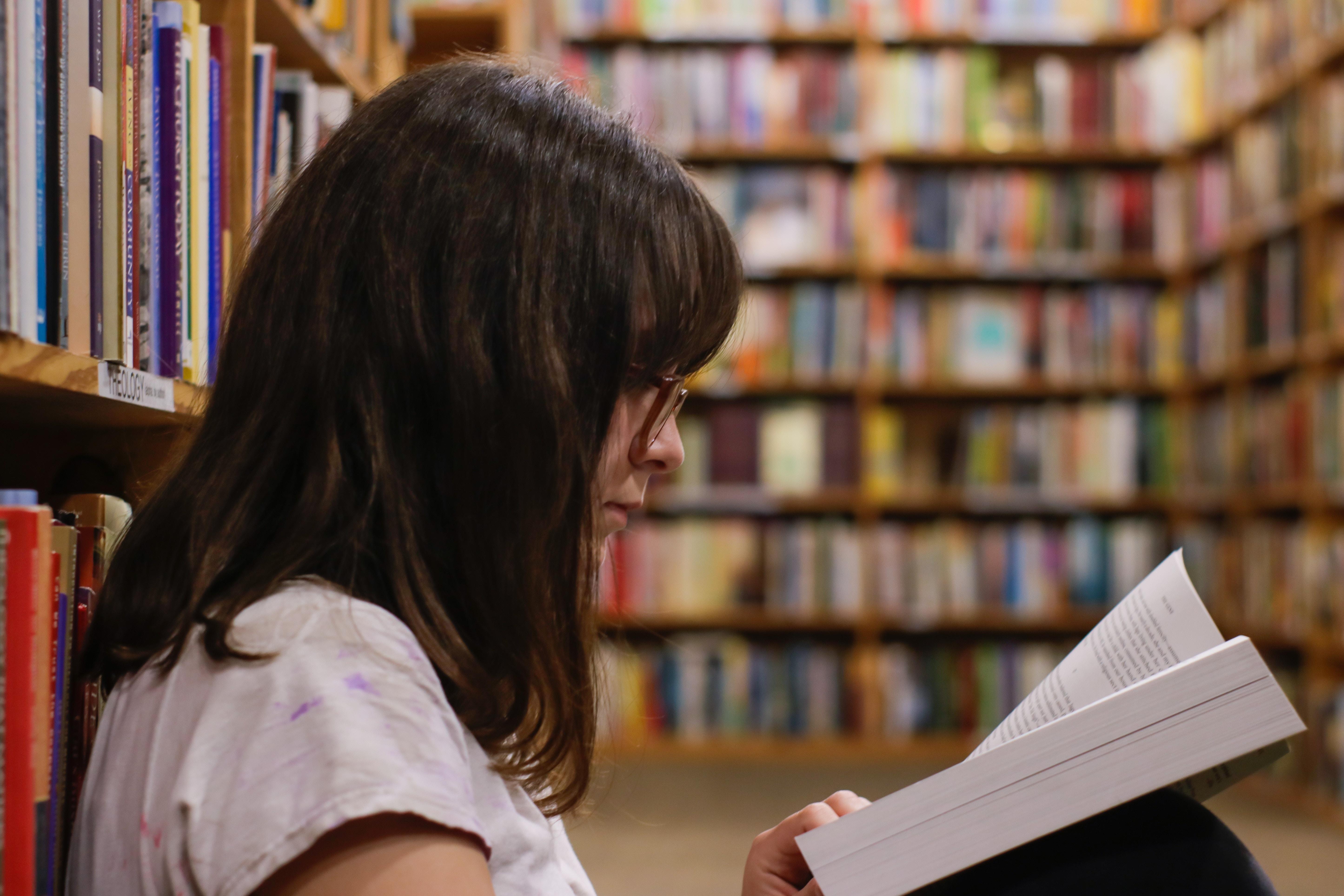 Tyttö lukee kirjaa kirjastossa